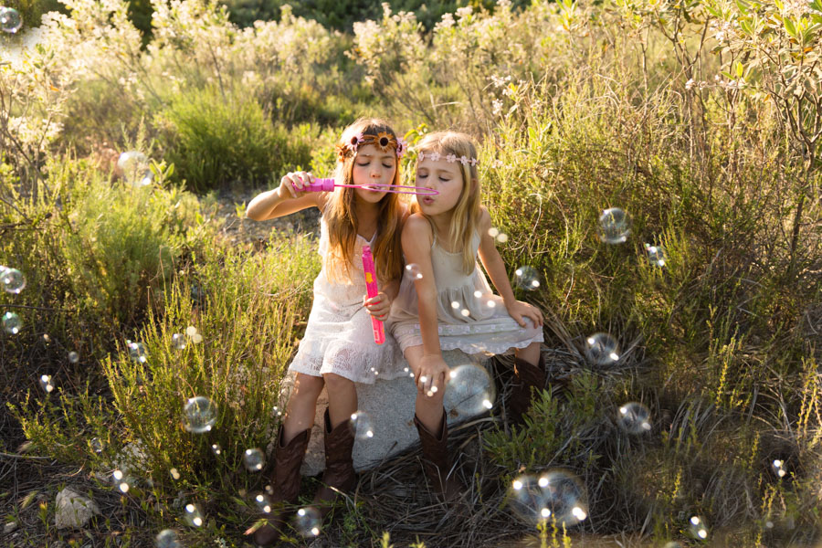 girls blowing bubbles, boho style, wild flowers and fields