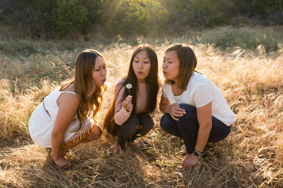 sisters blowing a dandelion